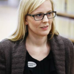 portrait picture of Angelica who is blond and has black glasses